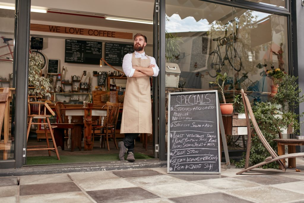 Full length shoot of a young barista standing in door of a coffee shop. Young man with beard wearing an apron standing with her arms crossed and looking away.